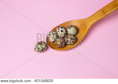 Quail Eggs On A Pink Background. Healthy Food. Quail Eggs Lie On A Wooden Spoon