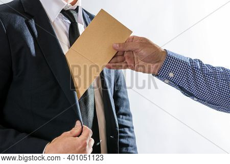 A Man Giving Bribe Money In A Brown Envelope To Another Businessman In A Corruption Scam. Bribery An
