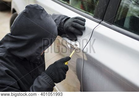 Car Thief In Action, A Man In A Hood Breaks A Screwdriver Car Door. The Man Dressed In Black Trying
