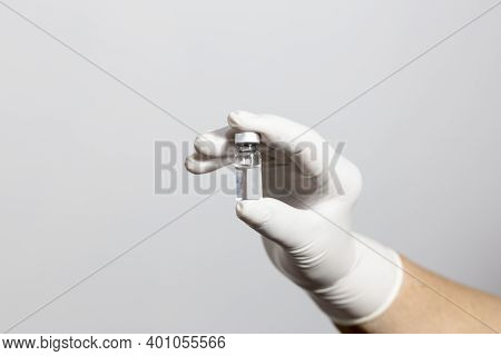 Lady Holding Vaccine Ampoule In Hand With Gloves