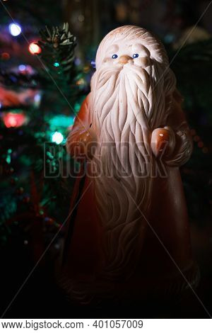 Toy Santa Claus Near A Decorated Christmas Tree With A Garland. Old Beautiful Traditional Rubber Fig