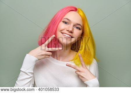 Head Shot Of Fashionable Beautiful Teenage Girl Showing Victory Gesture With Fingers, Female With Tr