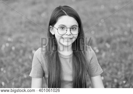 Small But Smart. Happy Small Girl Sit On Green Grass. Beauty Look Of Small Child. Small Baby Smile S