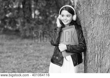 E-learning Courses. Happy Child Listen To Headphones. Small Girl Study Online Outdoors. E-learning.