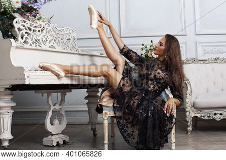 Young Pretty Brunette Ballet Dancer At Piano In Luxury Royal Interior, Lifestyle Rich People Concept