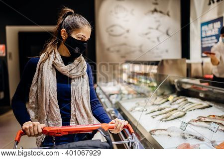 Young Woman Wearing Protective Face Mask Shopping In A Supermarket,buying Groceries.seafood And Fish