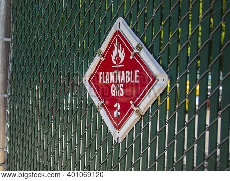 A Red And White Flammable Gas Warning Sign On A Fence