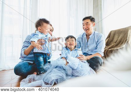 Happy Asian Family Smile And Laugh Together In Bedroom At Home. Two Parents And Children. People Lif