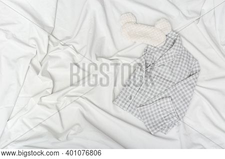 Warm Grey Pajamas And Fluffy Eye Mask On White Sheet. Cozy Accessories For Quiet Sleep. Sleepwear Fo