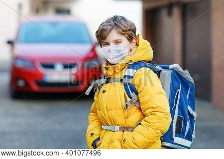 Little Kid Boy Wearing Medical Mask On The Way To School. Child Backpack Satchel. Schoolkid On Cold