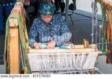 Chelyabinsk, Russia-September 12 2020. Folk art festival. A woman is hand-woven on a hand loom. The fabric is handmade.