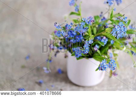 Bouquet Of Blue, Pink And White Forget-me-nots In A White Ceramic Mug On A Gray Concrete Background.