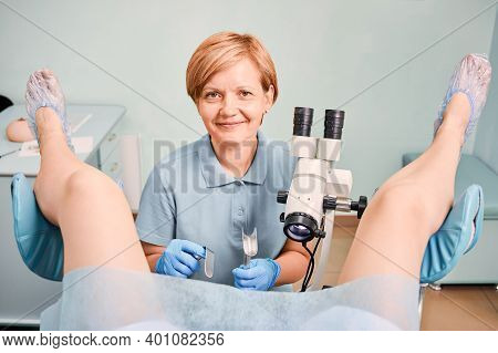 Female Doctor In Sterile Gloves Using Colposcope And Gynecological Retractors While Examining Woman