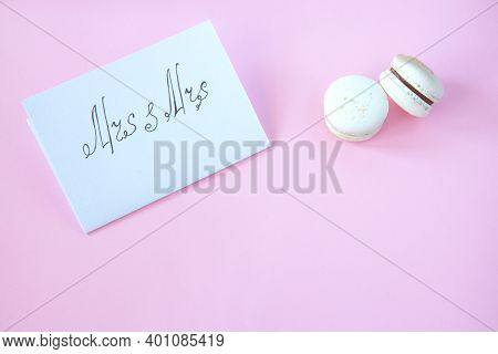 White Card With The Inscription Mrs And Mrs On A Pink Background. Sweets Macarons On A Bright Backgr