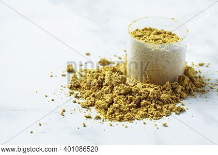 Vegan Hemp Protein Powder On White Marble Background. Vegan Protein Concept.