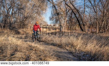 senior male biker is commuting on a gravel bike trail along the Poudre RIver  in Fort Collins, Colorado, fall or winter scenery