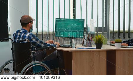 Disabled Businessman Sitting In Wheelchair With Protection Mask Cleaning Hands Before Checking Finan