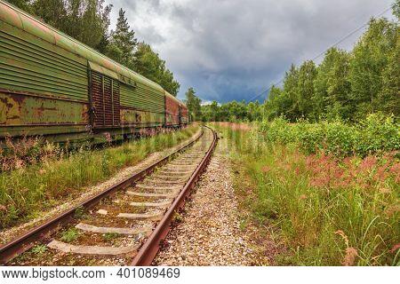 Obsolete railway wagons, abandoned on old railroad tracks ubder gloomy sky.