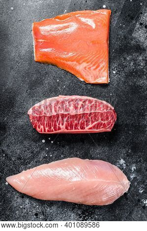 Different Types Of Raw Meat. Beef Top Blade, Salmon Fillet And Turkey Breast. Black Background. Top