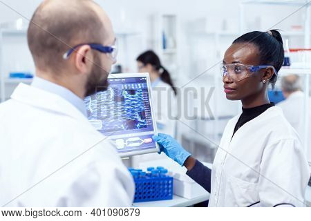 African Scientist Discussing Result Of Virus Research With Supervior In Laboratory Using Computer. M