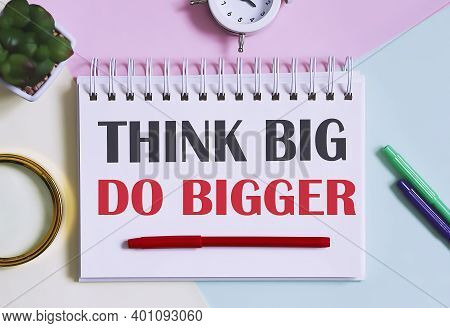 Think Big, Do Bigger Text Written On Notebook With Pencils, Magnifier