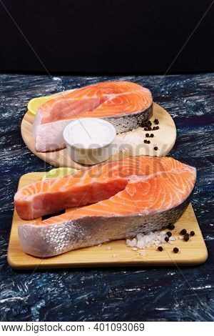 Salmon Steak, Rich In Omega 3 Oil, Lemon And Sea Salt On Black Background. Healthy And Diet Food.