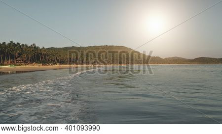 Sun over ocean bay waves aerial. Nobody nature seascape with green sea coast. Tropic forest at mountain of El Nido Island, Philippines, Asia. Cinematic summer vacation at paradise islet