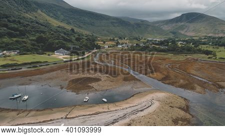 Landscape of mountains valley. Nobody nature seascape. Village at whisky distillery. Cinematic yachts, ships on ocean bay. Water of Loch Ranza bay, Arran Island, Scotland, United Kingdom, Europe