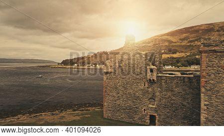 Closeup sun over castle ruins at sea bay aerial. Nobody nature seascape with boats. Historic heritage of United Kingdom. Cinematic Loch-Ranza, Arran island, Scotland, Europe. Cinematic drone shot