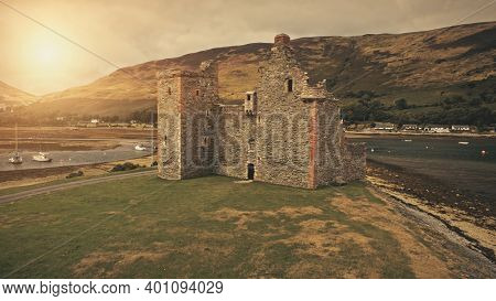Closeup castle ruins at sun sea coast aerial. Historical heritage of British culture. Ancient tourist attraction. History landmark close up. Cinematic Loch-Ranza Bay, Arran island, Scotland, Europe
