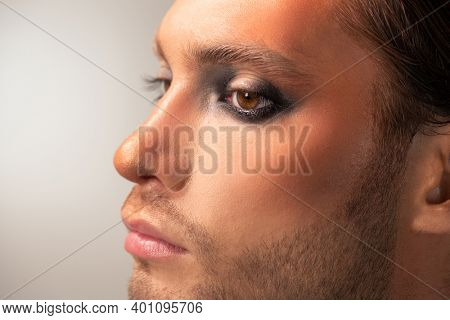Side view of part of face of serious young male fashion model with stage makeup standing in front of camera with copyspace on the left
