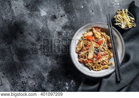 Udon Stir-fry Noodles With Chicken Meat And Sesame. Black Background. Top View. Copy Space