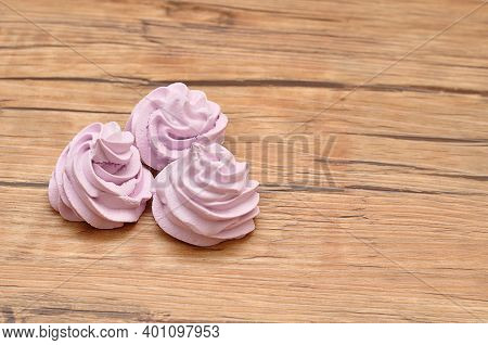 Three Purple Meringues On A Wooden Table
