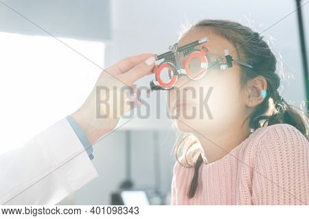 Elementary schoolgirl sitting in front of ophthalmologist during check-up of her eyesight with optometrist trial frame in contemporary clinics