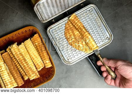 Cooking Waffles At Home - Waffle Maker. A Mans Hand Rolls A Wafer. Ready-made Waffles On A Plate. Cu