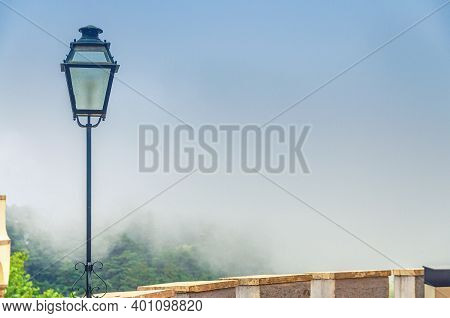 Iron Vintage Lantern Lamp And Merlons Of Old Castle Building With Green Forest In Fog Background, Co