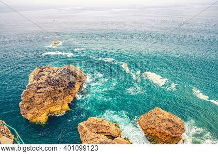 Top Aerial View Of Waves Crashing Cliffs And Small Rock Islands In Azure Turquoise Water Of Atlantic