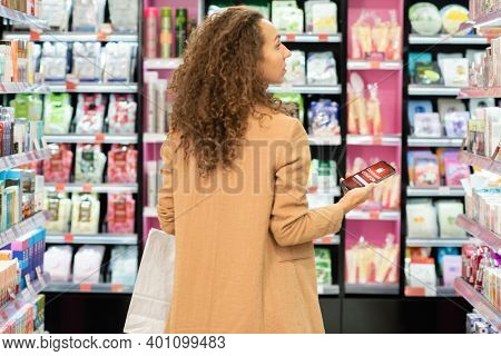 Young elegant curly female customer with paperbag and smartphone with discount coupon standing among large displays with beauty products