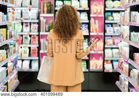 Back view of young curly female customer with paperbag using smartphone while standing among large displays with beauty products