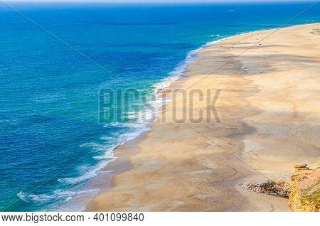 Top Aerial Panoramic View Of Sandy Beach, Waves Of Azure Blue Water Of Atlantic Ocean And Endless Ho