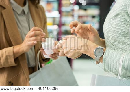 Hands of two young elegant consumers with paperbags applying cosmetic cream while testing it in beauty shop and choosing which to buy