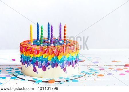 Multicolored Birthday Cake Decorated With Cream And Candles. Birthday Party Concept.