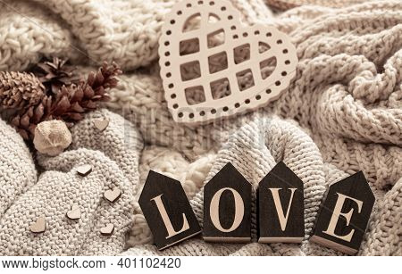 Wooden Letters Make Up The Word Love On A Background Of Cozy Knitted Items. Valentine's Day Holiday