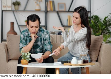 Confused Unhappy Young Woman Showing Pile Of Unpaid Bills To Pensive Boyfriend