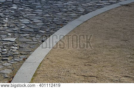 Contrast Between Gray Basalt Paving For Cars And Soft Gravel Road For Pedestrians Made Of Beige Sand