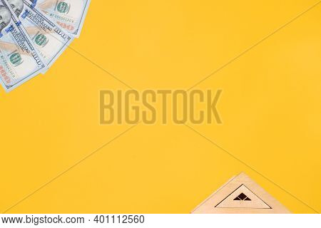 Toy Roof Of House And One Hundred Dollar Bills On Yellow Background, Flat Lay. Concept Cost Of Real