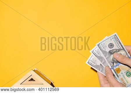 Male Hands Holding Money And Toy Roof Of The House, Yellow Background. Buying A House, Real Estate P