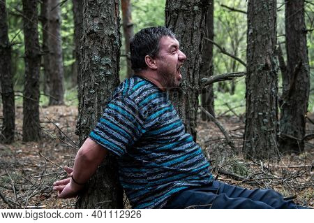 A Hostage In The Woods. A Man In A Blue T-shirt And Trousers Is Sitting On The Ground Tied To A Tree