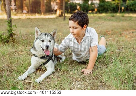 Portrait Of Happy Caucasian Boy With His Doggy Lying On Lawn. Kid Playing With His Puppy In The Park