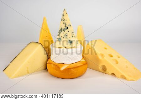 Different Types Of Delicious Cheese On Grey Background. Blue Cheese Dorblu, Smoked Suluguni, Brie, M